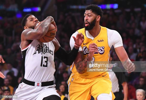 Anthony Davis of the Los Angeles Lakers guards Paul George of the Los Angeles Clippers as he drives to the basket in the first quarter of the game at...
