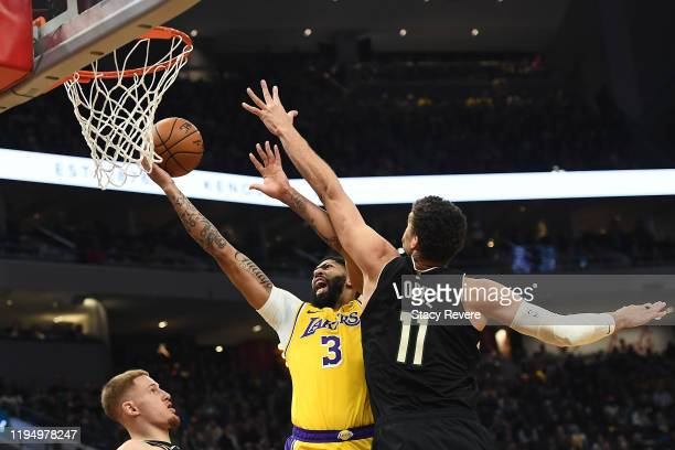 Anthony Davis of the Los Angeles Lakers is fouled by Brook Lopez of the Milwaukee Bucks during the second half of a game at Fiserv Forum on December...