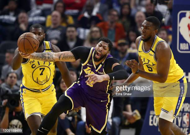 Anthony Davis of the Los Angeles Lakers is fouled by Kevon Looney of the Golden State Warriors at Chase Center on February 27 2020 in San Francisco...