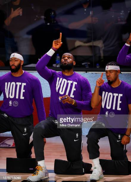 Anthony Davis of the Los Angeles Lakers, LeBron James of the Los Angeles Lakers and Quinn Cook of the Los Angeles Lakers kneel during the National...