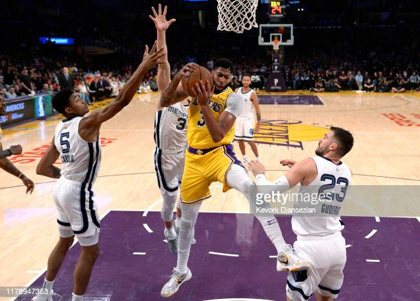 Anthony Davis of the Los Angeles Lakers pulls down a rebound against Bruno Caboclo Marko Guduric and Grayson Allen of the Memphis Grizzlies during...