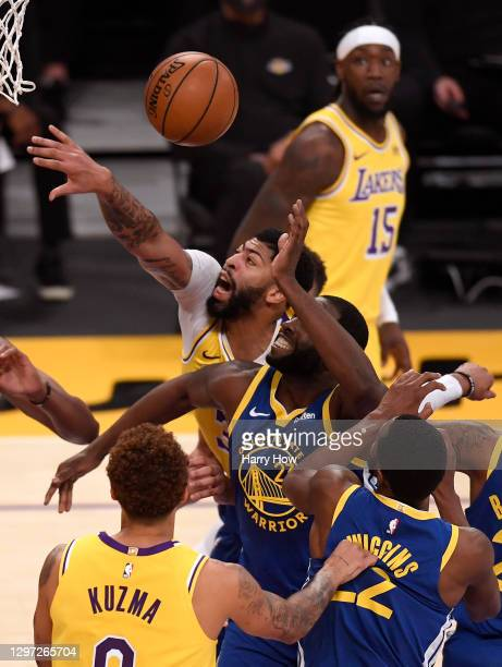 Anthony Davis of the Los Angeles Lakers reaches for the ball behind Draymond Green of the Golden State Warriors during a 115-113 loss to the Golden...