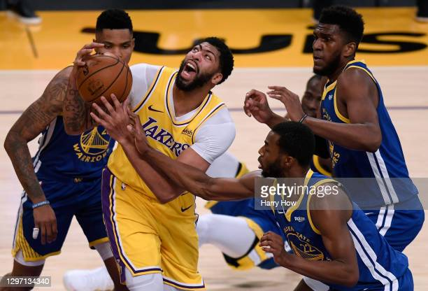 Anthony Davis of the Los Angeles Lakers reacts as he grabs a rebound between Kent Bazemore, Andrew Wiggins and Kevon Looney of the Golden State...