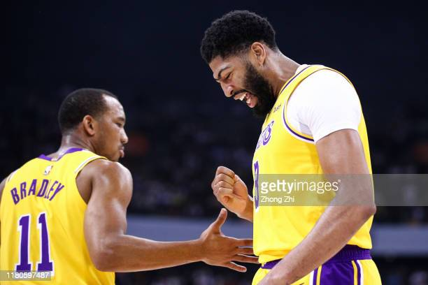 Anthony Davis of the Los Angeles Lakers reacts with team mate Avery Bradley during the match against the Brooklyn Nets during a preseason game as...