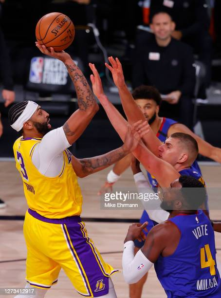 Anthony Davis of the Los Angeles Lakers shoots against Nikola Jokic and Paul Millsap of the Denver Nuggets during the third quarter in Game One of...