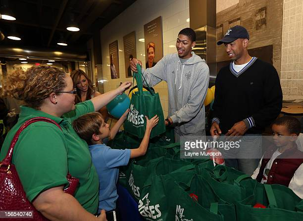 Anthony Davis of the New Orleans Hornets and Monty Williams distribute Thanksgiving baskets provided by the Hornets and Rouses to Emerge students on...