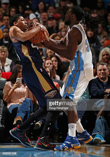 Anthony Davis of the New Orleans Pelicans and Kenneth Faried of the Denver Nuggets come to a stand off and a jump ball at Pepsi Center on November 21...