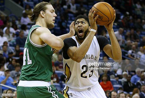 Anthony Davis of the New Orleans Pelicans drives against Kelly Olynyk of the Boston Celtics during the second half of a game at the Smoothie King...