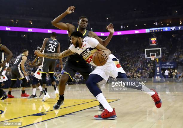 Anthony Davis of the New Orleans Pelicans drives on Kevon Looney of the Golden State Warriors at ORACLE Arena on January 16 2019 in Oakland...