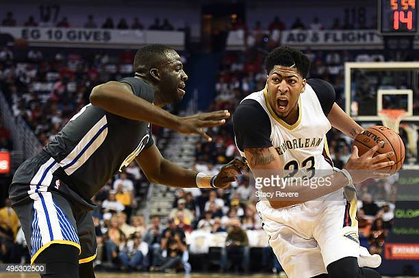 Anthony Davis of the New Orleans Pelicans drives to the basket against Draymond Green of the Golden State Warriors during a game at the Smoothie King...