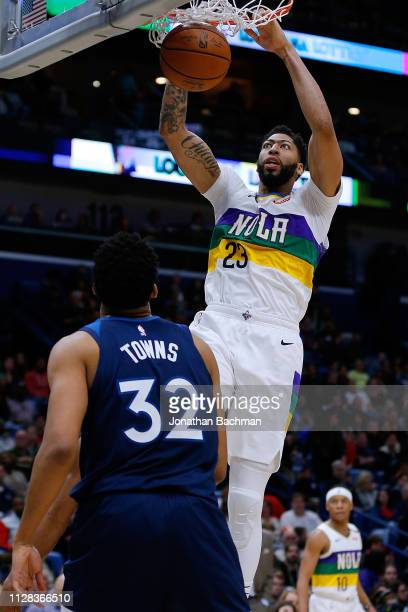 Anthony Davis of the New Orleans Pelicans dunks over KarlAnthony Towns of the Minnesota Timberwolves during the first half at the Smoothie King...
