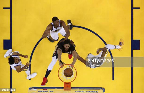 Anthony Davis of the New Orleans Pelicans goes up for a dunk on Quinn Cook Kevon Looney and Kevin Durant of the Golden State Warriors during Game...