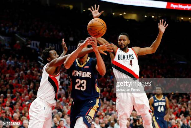 Anthony Davis of the New Orleans Pelicans is guarded by AlFarouq Aminu and Maurice Harkless of the Portland Trail Blazers during Game One of the...