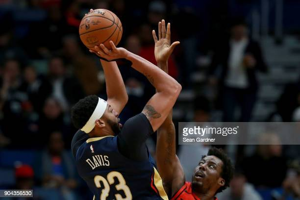 Anthony Davis of the New Orleans Pelicans shoots over AlFarouq Aminu of the Portland Trail Blazers during the first half at the Smoothie King Center...