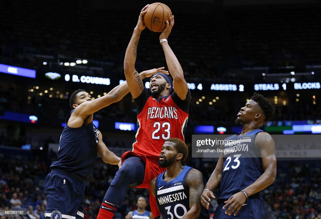 Anthony Davis #23 of the New Orleans Pelicans shoots over Jimmy Butler #23 of the Minnesota Timberwolves, Karl-Anthony Towns #32 and Aaron Brooks #30 during the first half of a game at the Smoothie King Center on November 29, 2017 in New Orleans, Louisiana.