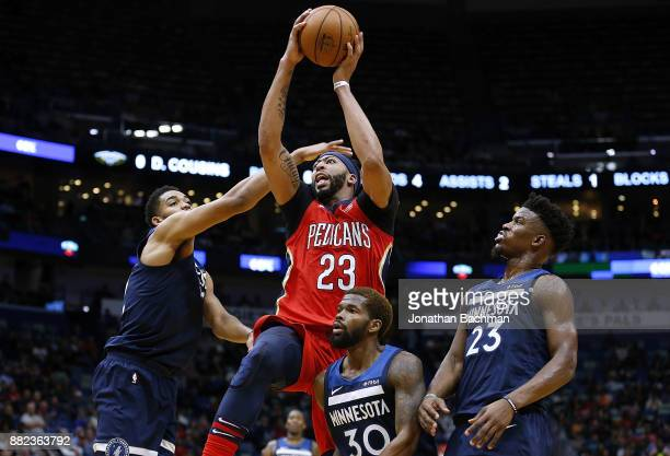 Anthony Davis of the New Orleans Pelicans shoots over Jimmy Butler of the Minnesota Timberwolves KarlAnthony Towns and Aaron Brooks during the first...