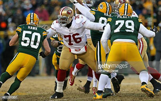 Anthony Davis of the San Fransico 49ers blocks A.J. Hawk and Ryan Pickett of the Green Bay Packers during an NFC Wild Card Playoff game at Lambeau...