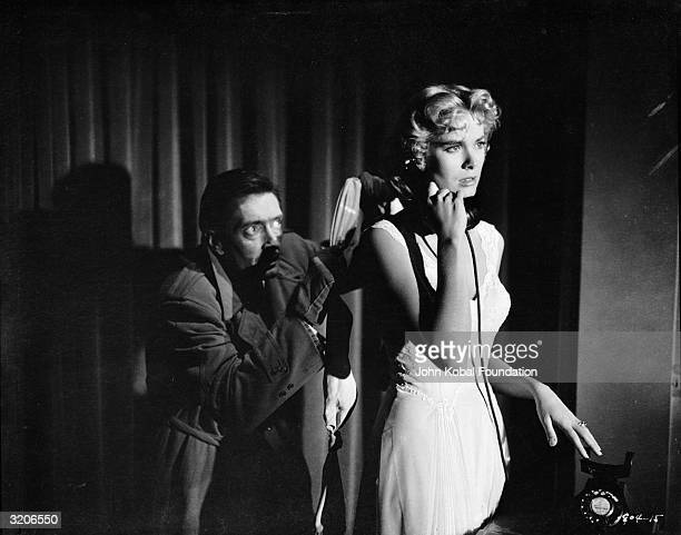 Anthony Dawson sneaks up behind an oblivious Grace Kelly in a tense scene from the film 'Dial M For Murder' directed by Alfred Hitchcock