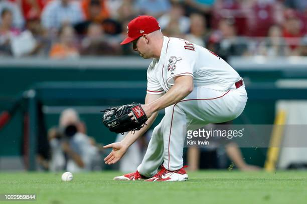 Anthony DeSclafani of the Cincinnati Reds fields a ground ball during the game against the San Francisco Giants at Great American Ball Park on August...