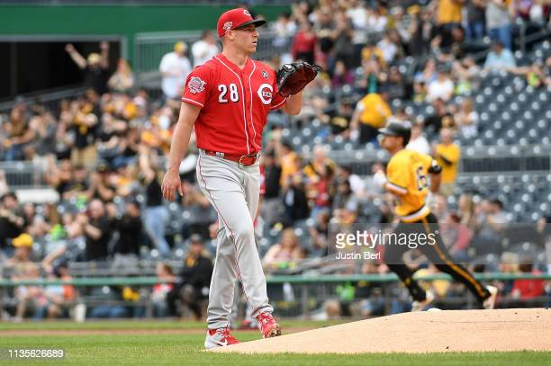Anthony DeSclafani of the Cincinnati Reds reacts as Adam Frazier of the Pittsburgh Pirates rounds the bases after hitting a solo home run in the...