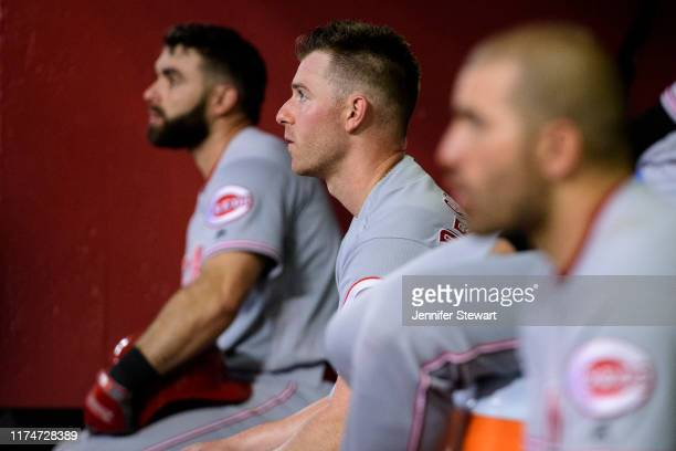 Anthony DeSclafani of the Cincinnati Reds sits in between Jose Peraza and Joey Votto during the MLB game against the Arizona Diamondbacks at Chase...
