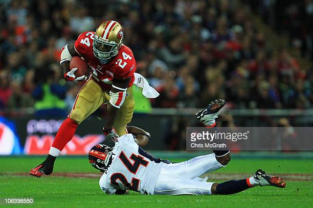 Anthony Dixon of San Francisco 49ers is tackled by Champ Bailey of Denver Broncos during the NFL International Series match between Denver Broncos...