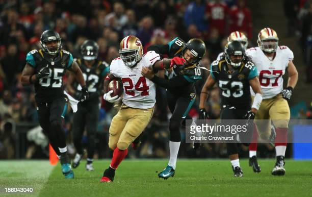 Anthony Dixon of the San Francisco 49ers is challenged by Josh Scobee of the Jacksonville Jaguars during the NFL International Series game between...