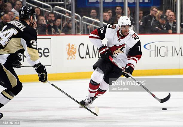 Anthony Duclair of the Arizona Coyotes moves the puck up ice in front of Tom Kuhnhackl of the Pittsburgh Penguins at Consol Energy Center on February...