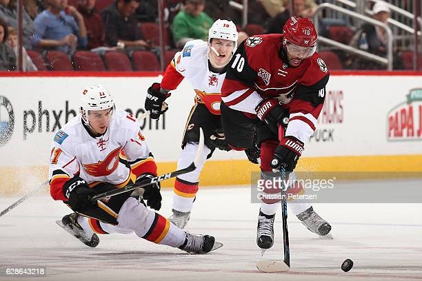 Anthony Duclair of the Arizona Coyotes skates with the puck ahead of Mikael Backlund and Matthew Tkachuk of the Calgary Flames during the first...