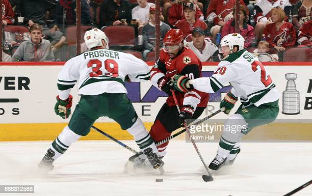 Anthony Duclair of the Arizona Coyotes skates with the puck between Nate Prosser and Ryan Suter of the Minnesota Wild during the first period at Gila...