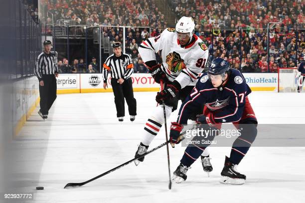 Anthony Duclair of the Chicago Blackhawks and Josh Anderson of the Columbus Blue Jackets battle for a loose puck during the third period of a game on...