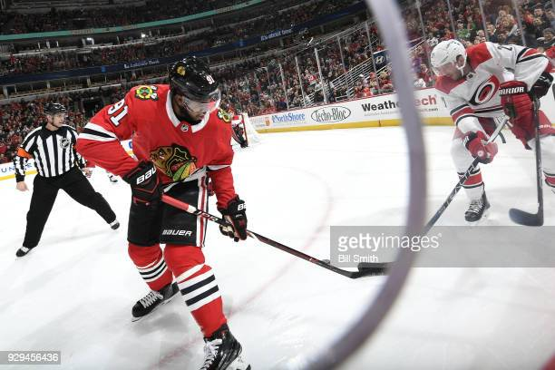 Anthony Duclair of the Chicago Blackhawks and Lee Stempniak of the Carolina Hurricanes battle for the puck in the first period at the United Center...