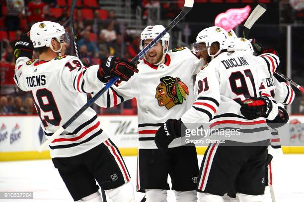 Anthony Duclair of the Chicago Blackhawks celebrates his first period goal with Jonathan Toews and Jordan Oesterle while playing the Detroit Red...