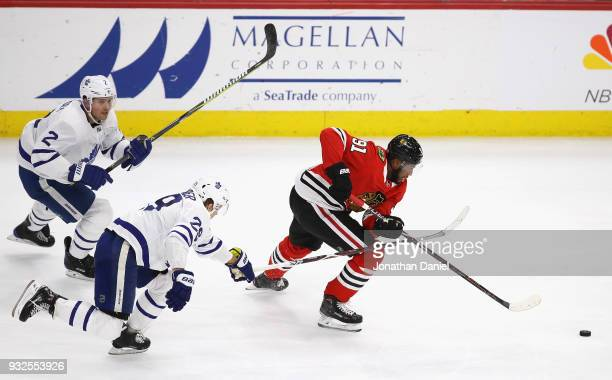 Anthony Duclair of the Chicago Blackhawks chases the puck followed by Ron Hainsey and William Nylander of the Toronto Maple Leafs at the United...