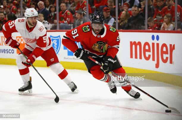 Anthony Duclair of the Chicago Blackhawks looks to pass next to Frans Nielsen of the Detroit Red Wings at the United Center on January 14 2018 in...