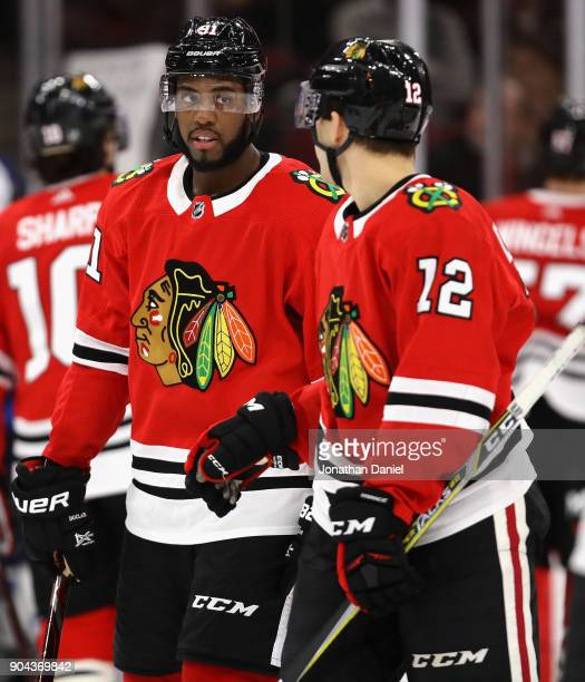 Anthony Duclair of the Chicago Blackhawks talks with teammate Alex DeBrincat as they skate to their positions on the ice against the Winnipeg Jets at...