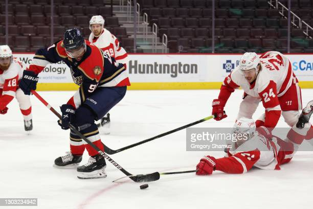 Anthony Duclair of the Florida Panthers tries to get past the sticks of Dylan Larkin and Jon Merrill of the Detroit Red Wings during the third period...