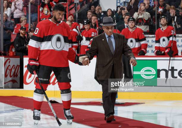 Anthony Duclair of the Ottawa Senators escorts Willie O'Ree for a ceremonial face-off as part of Black History Month initiatives prior to a game...