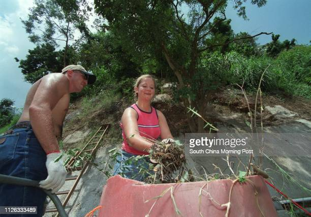 DC2 Anthony Duncan and HM3 Amanda Wardleigh US Navy sailors from the USS Curtis Wilbur help cut grass clear mud and trim trees on August 27 2002 as...