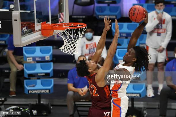 Anthony Duruji of the Florida Gators dunks the ball over Keve Aluma of the Virginia Tech Hokies during overtime in the first round of the 2021 NCAA...