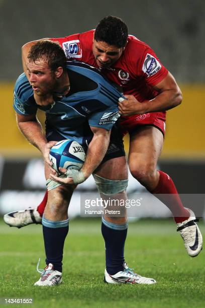 Anthony Faingaa of the Reds hangs onto Luke Braid of the Blues during the round 10 Super Rugby match between the Blues and the Reds at Eden Park on...