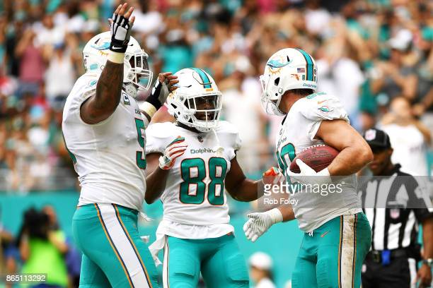 Anthony Fasano of the Miami Dolphins celebrates with Leonte Carroo and Minke Pouncey after scoring a touchdown during the second quarter against the...