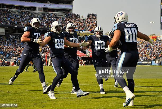 Anthony Fasano of the Tennessee Titans is congratulated by teammates Phillip Supernaw and Brian Schwenke after scoring a touchdown against the Green...