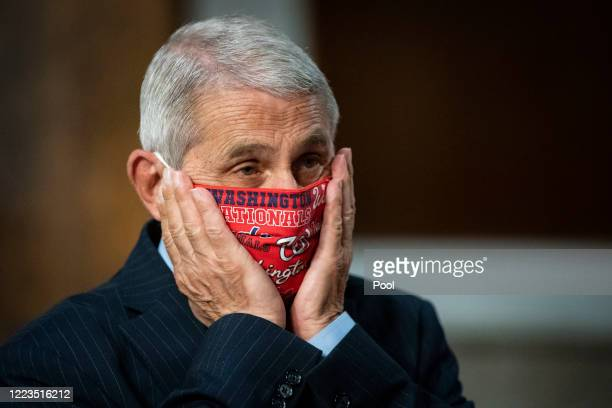 Anthony Fauci, director of the National Institute of Allergy and Infectious Diseases, adjusts a Washington Nationals protective mask while arriving...
