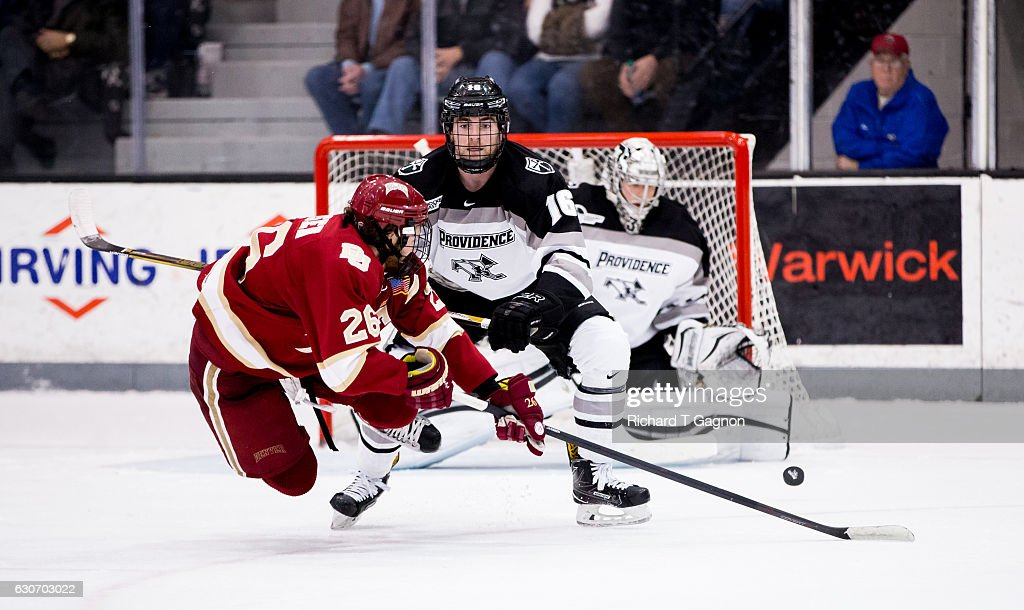 Anthony Florentino #16 of the Providence College Friars checks Evan Janssen #26 of the Denver Pioneers as he shoots the puck towards Hayden Hawkey #31 during NCAA hockey at the Schneider Arena on December 30, 2016 in Providence, Rhode Island. The game ended in a 2-2 tie.
