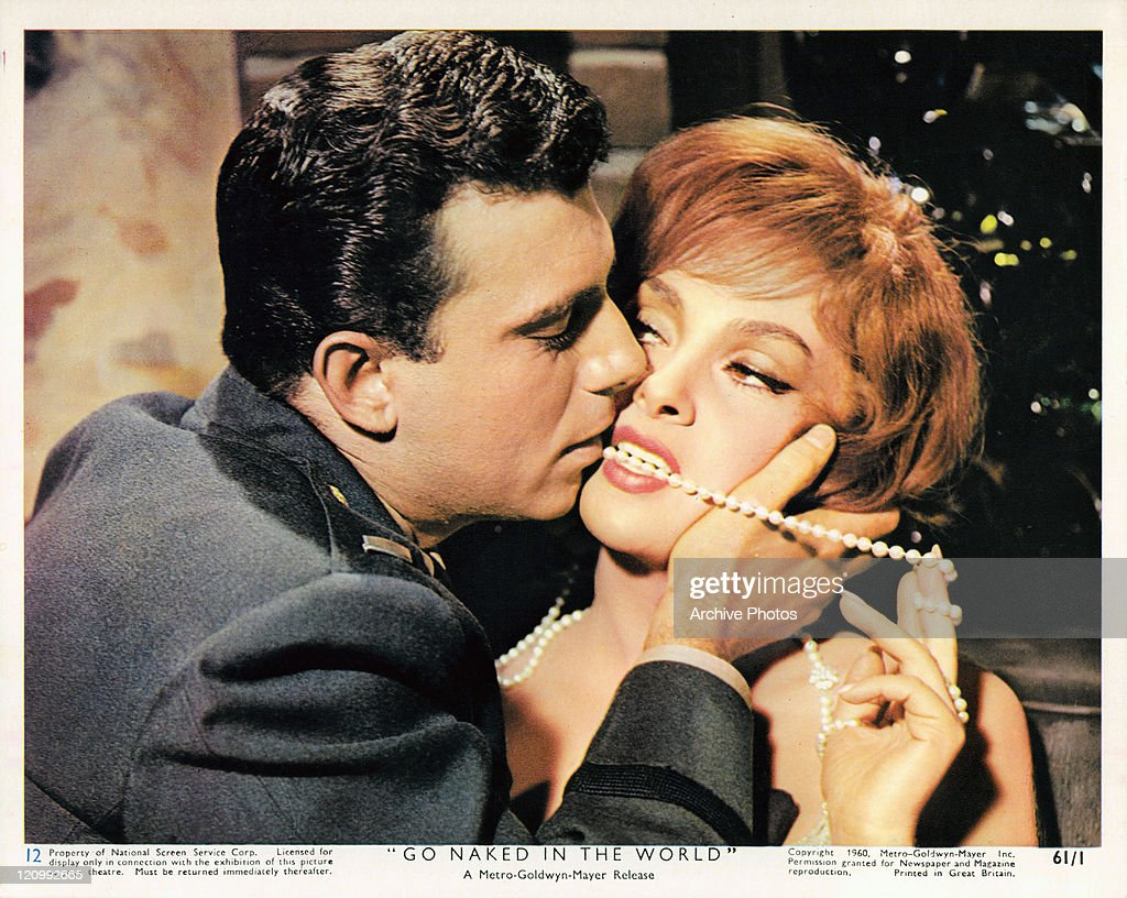 Anthony Franciosa kisses the face of Gina Lollobrigida who has a pearl necklace between her teeth in a scene from the film 'Go Naked In The World', 1961.