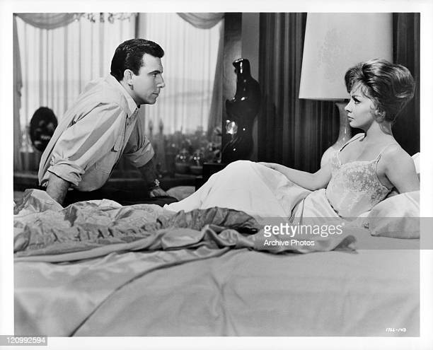 Anthony Franciosa sitting on bed talking with Gina Lollobrigida in a scene from the film 'Go Naked In The World' 1961