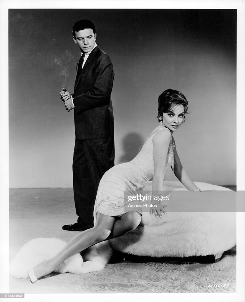 Anthony Franciosa standing holding cigarette peering down at Gina Lollobrigida lying on fur chair in a scene from the film 'Go Naked In The World', 1961.