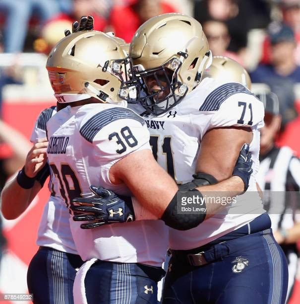 Anthony Gargiulo of the Navy Midshipmen congratulated by Evan Martin after he scored against the Houston Cougars in the first half on November 24...