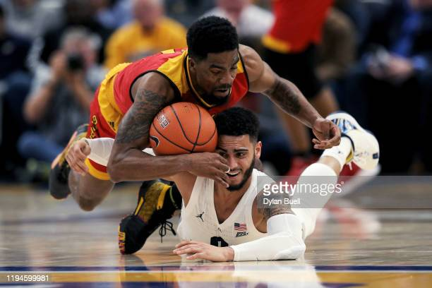 Anthony Gaston of the Grambling State Tigers and Markus Howard of the Marquette Golden Eagles battle for a loose ball in the first half at the Fiserv...
